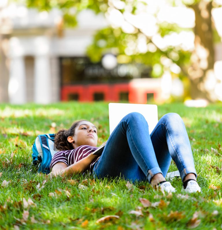 Student lays in grass on laptop